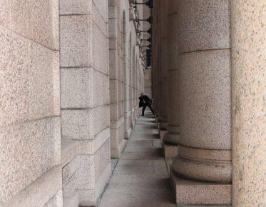 Mies kiiruhtaa sisään Eduskuntataloon