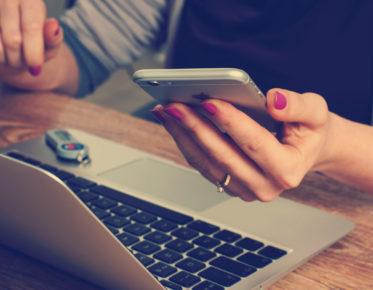 naisen käsi pitelee kännykkää